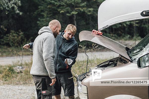 Kanada  British Columbia  zwei Männer kontrollieren den Ölstand des Minivans.