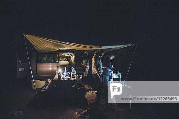 Kanada  British Columbia  zwei Männer kochen nachts unter der Plane im Minivan.