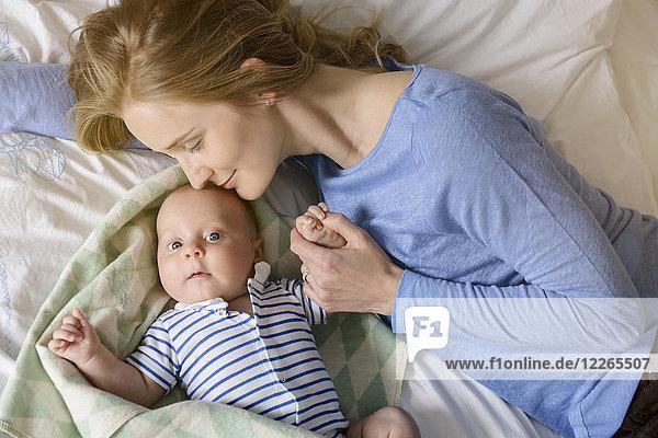 Mutter mit ihrem kleinen Jungen  der die Hände auf dem Bett hält.