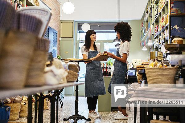 Zwei lächelnde Frauen  die in einem Laden mit Zwischenablage stehen.