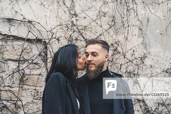 Junge Frau küsst Freund auf die Wange