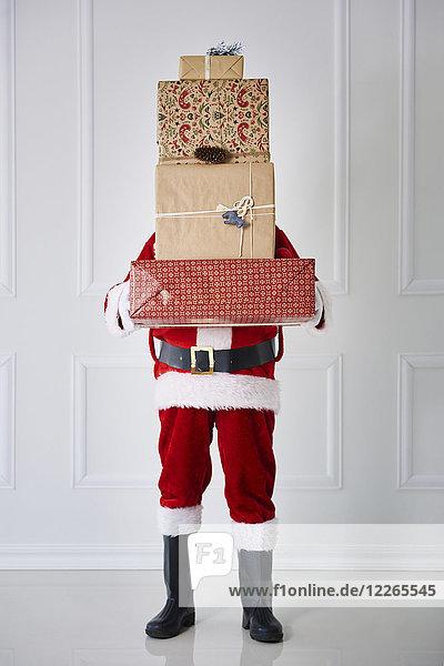 Weihnachtsmann mit Weihnachtsgeschenken im Stapel