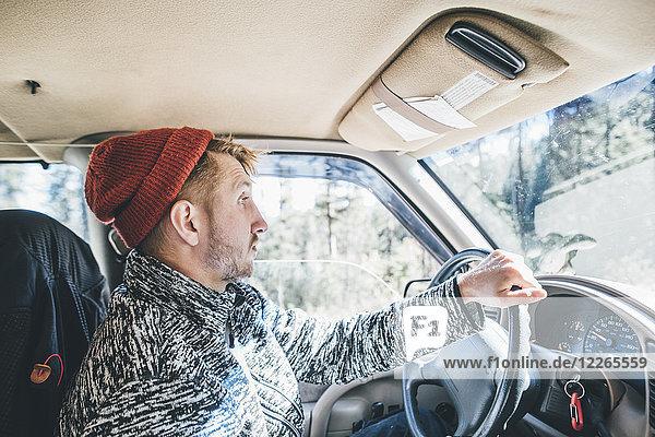 Junger Mann mit Wollmütze und Bart auf Roadtrip