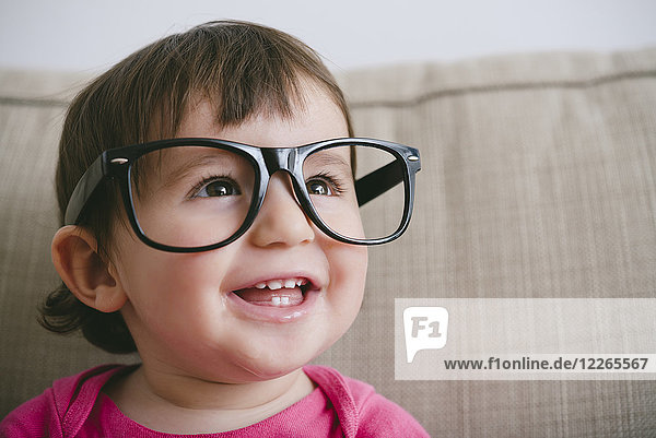 Portrait of laughing baby girl wearing oversized glasses