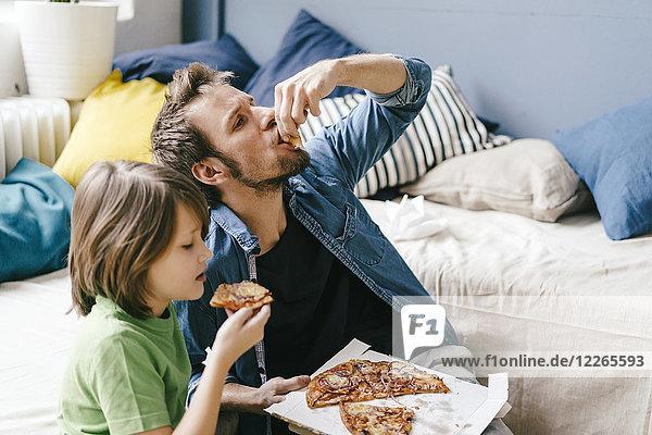 Vater und Sohn essen Pizza zu Hause