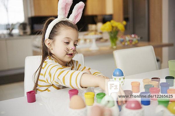 Mädchen mit Hasenohren am Tisch sitzend Ostereier bemalend