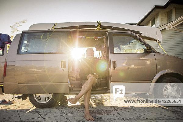 Barfuss-Mann im Minivan im Gegenlicht mit Handy