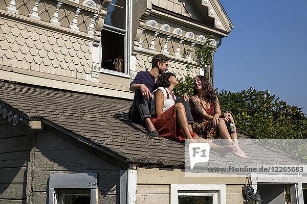 Glückliche Freunde sitzen auf dem Dach