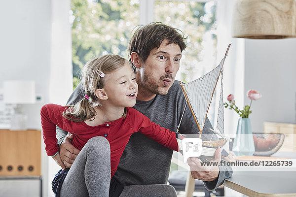 Glücklicher Vater und Tochter beim Spielen mit dem Modellboot zu Hause