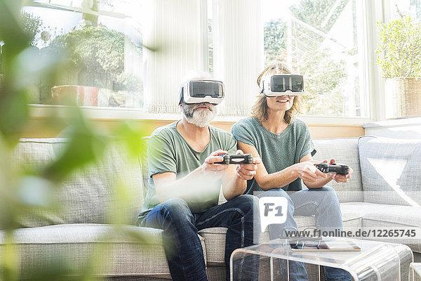 Ein reifes Paar  das zu Hause auf der Couch sitzt und eine VR-Brille trägt und ein Videospiel spielt.