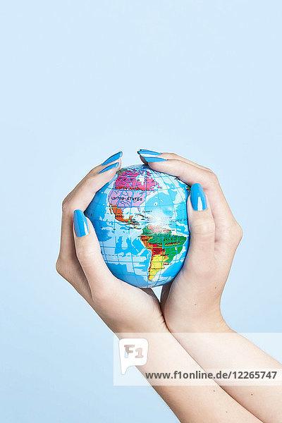 Nahaufnahme der Frauenhände  die den Globus halten