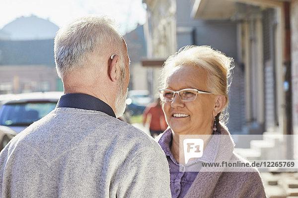 Nahaufnahme eines älteren Mannes mit Hörgerät im Gespräch mit einer älteren Frau