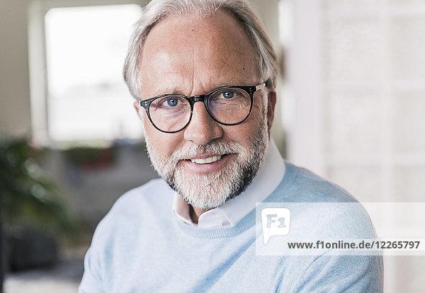 Porträt eines lächelnden reifen Mannes mit grauen Haaren und Bart mit Brille