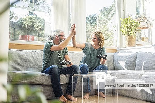 Glückliches reifes Paar  das zu Hause auf der Couch sitzt und Videospiele spielt.