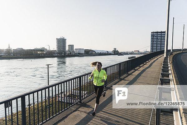 Junge Frau läuft auf Brücke am Flussufer