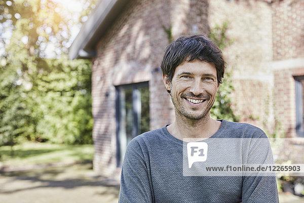 Porträt eines lächelnden Mannes vor seinem Haus