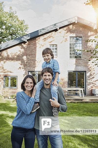 Porträt einer glücklichen Familie mit Sohn im Garten ihres Hauses