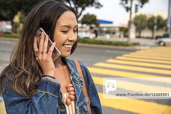 Lächelnde junge Frau spricht auf dem Smartphone auf der Straße