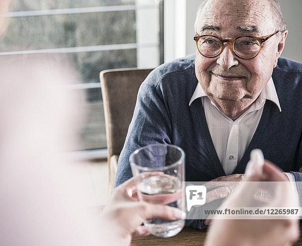 Frau hält Pille und Glas Wasser für lächelnden älteren Mann