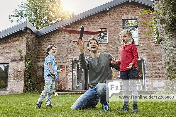 Vater mit zwei Kindern  die mit einem Spielzeugflugzeug im Garten ihres Hauses spielen.