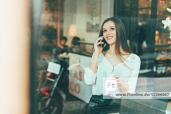 Porträt einer glücklichen jungen Frau am Telefon in einem Coffee-Shop