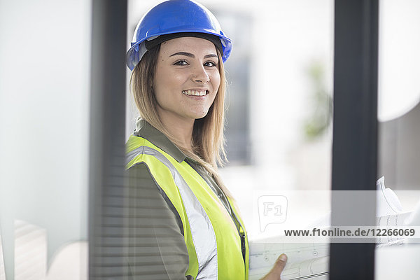 Portrait of smiling woman wearing hard hat and reflective jacket
