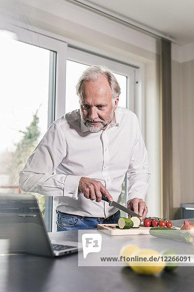 Reifer Mann  der Gemüse in der Küche zubereitet  während er sich den Laptop ansieht.