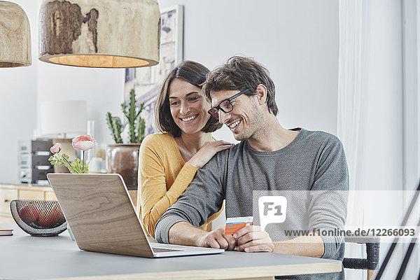 Glückliches Paar mit einer Karte mit Laptop auf dem Tisch zu Hause