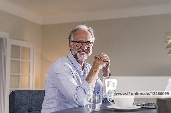 Portrait eines glücklichen reifen Mannes mit Laptop und Tasse Kaffee am Tisch in seinem Wohnzimmer