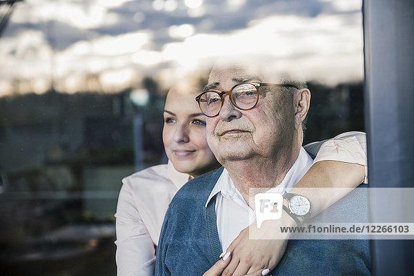Porträt einer jungen Frau  die den älteren Mann am Fenster umarmt.