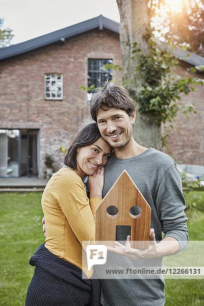Porträt eines lächelnden Ehepaares im Garten ihres Hausmodells