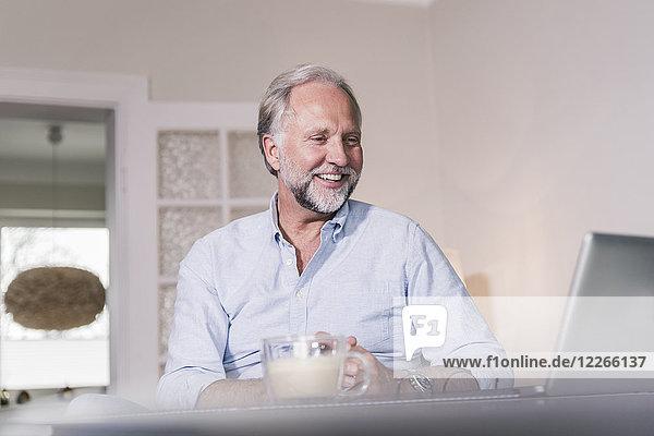 Porträt eines glücklichen Mannes mit Blick auf den Laptop