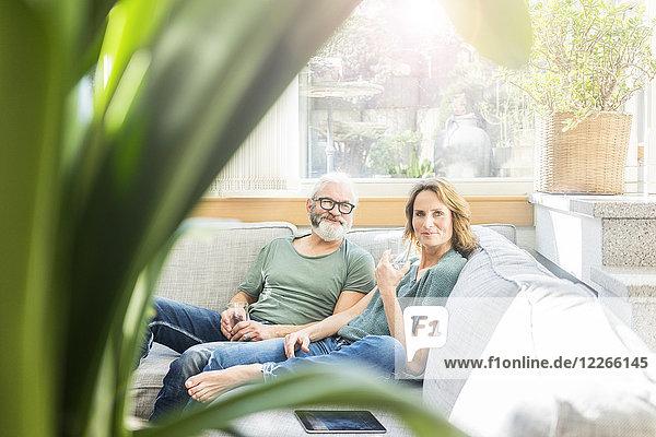 Ein reifes Paar entspannt sich zu Hause auf der Couch.