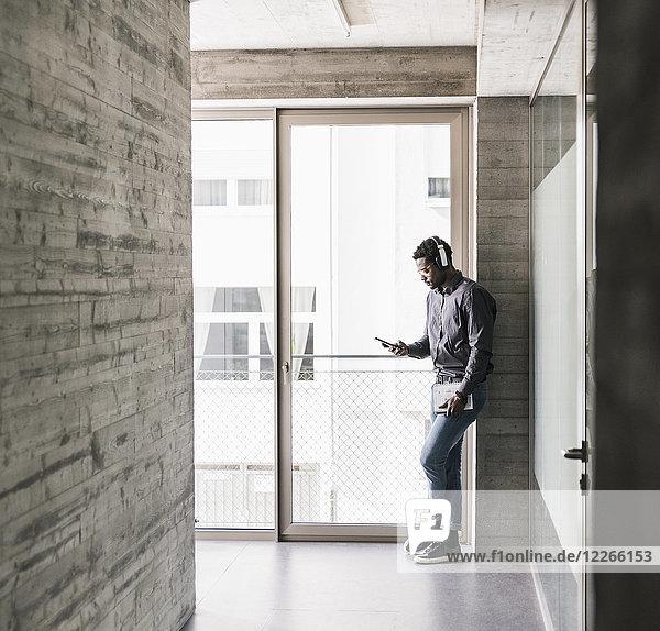 Geschäftsmann mit Kopfhörer und Blick aufs Handy am Fenster
