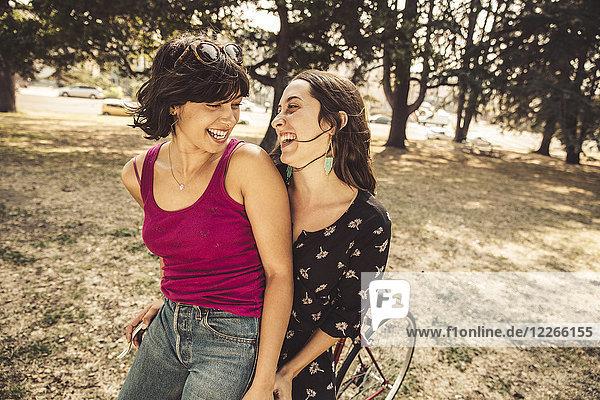 Zwei glückliche junge Frauen auf dem Fahrrad
