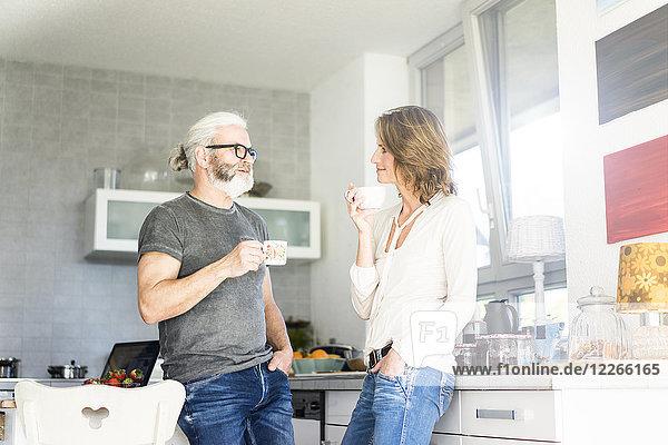Reife Paare trinken Kaffee in der Küche zu Hause