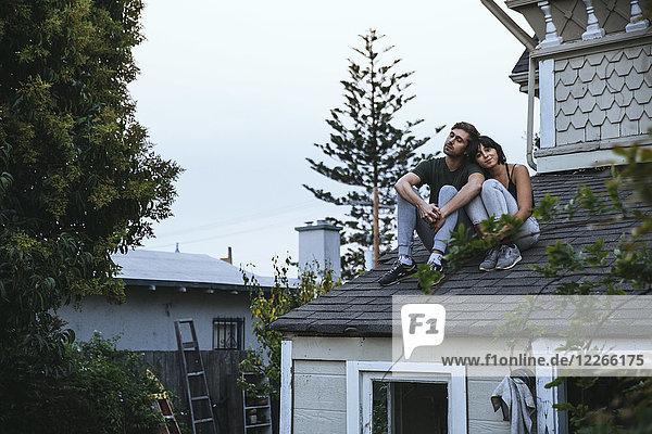 Entspanntes Paar auf dem Dach sitzend