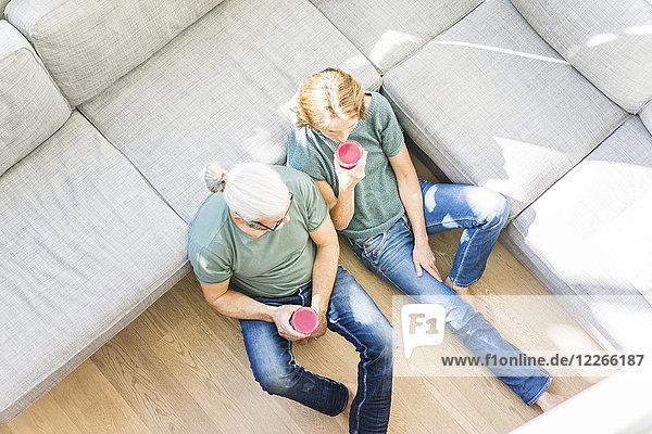 Erwachsenes Paar mit gesunden Getränken im heimischen Wohnzimmer