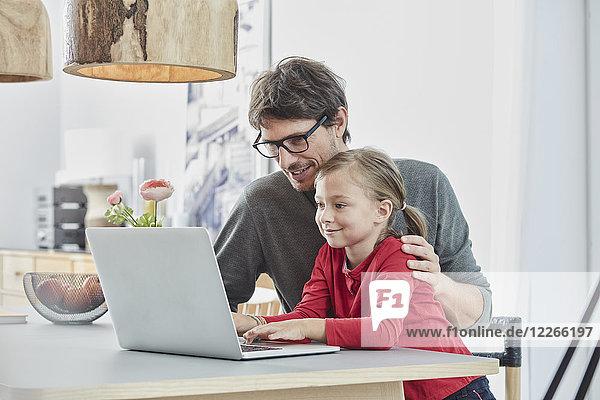 Lächelnder Vater und Tochter mit Laptop auf dem Tisch zu Hause
