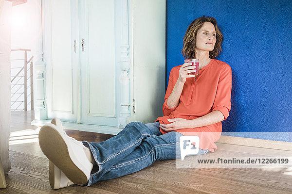 Entspannte Frau zu Hause auf dem Boden sitzend mit gesundem Getränk