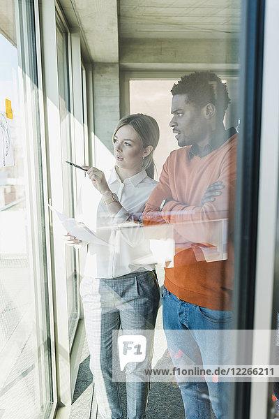 Gelegentliche Geschäftsfrau und Geschäftsmann im Gespräch am Fenster