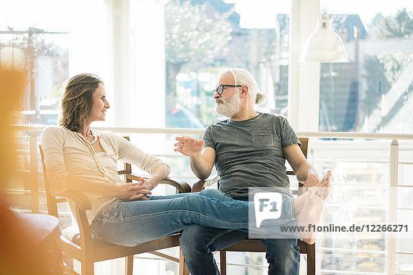 Entspanntes  reifes Paar im Gespräch auf Stühlen zu Hause