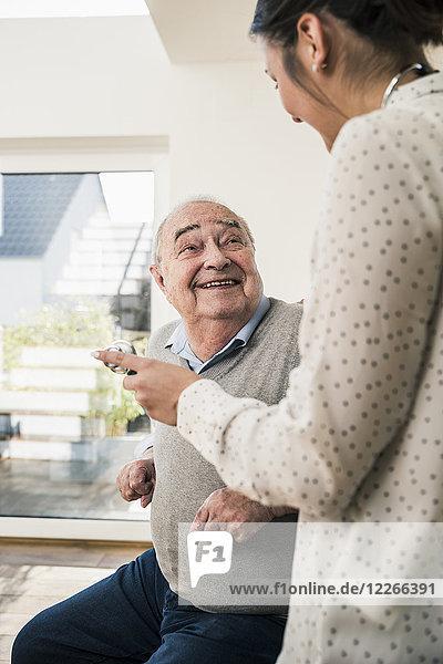 Älterer Mann lächelt Krankenschwester mit Stethoskop zu Hause an