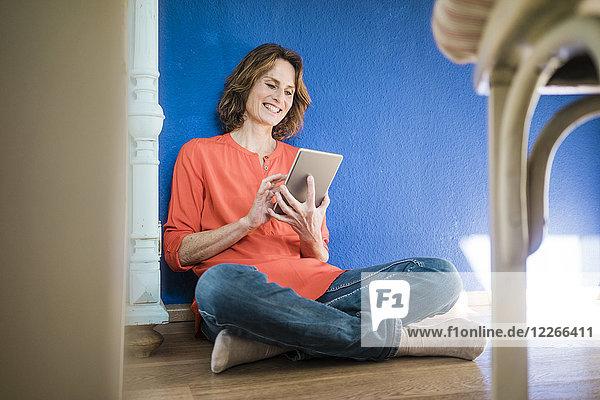 Lächelnde Frau  die zu Hause auf dem Boden sitzt und Tabletten benutzt.