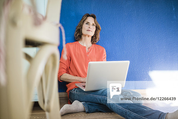 Frau sitzt zu Hause auf dem Boden mit Laptop