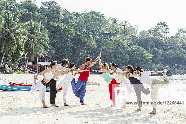 Thailand  Koh Phangan  eine Gruppe von Menschen  die Yoga am Strand machen.