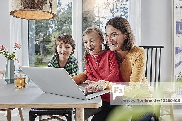 Glückliche Mutter mit zwei Kindern mit Laptop zu Hause