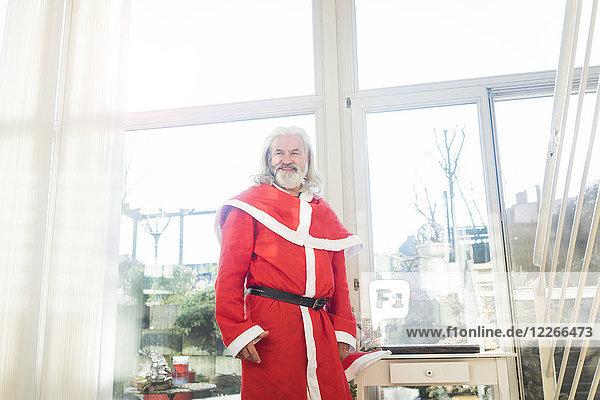 Lächelnder bärtiger reifer Mann im Weihnachtsmann-Kostüm