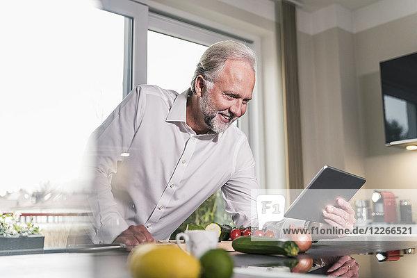 Lächelnder reifer Mann mit Tablette in der Küche