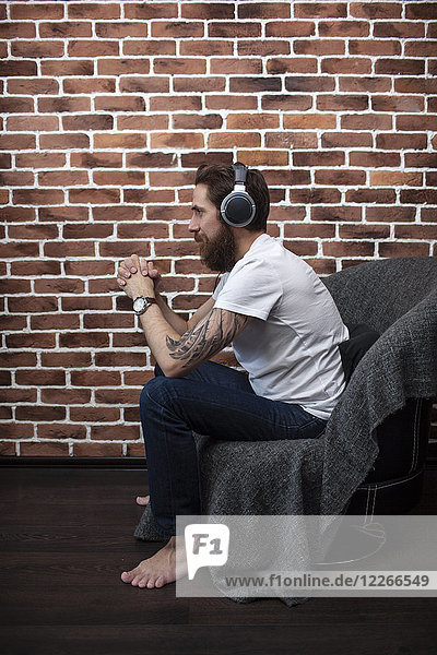 Tätowierter Mann sitzt auf einem Sessel und hört Musik mit Kopfhörern.